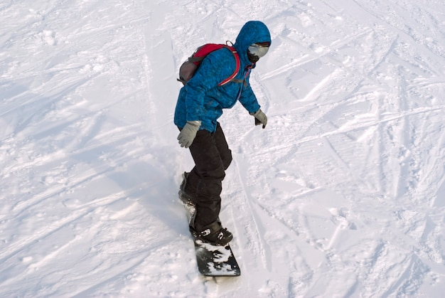 O snowboarder está andando em uma montanha nevada, vista de cima