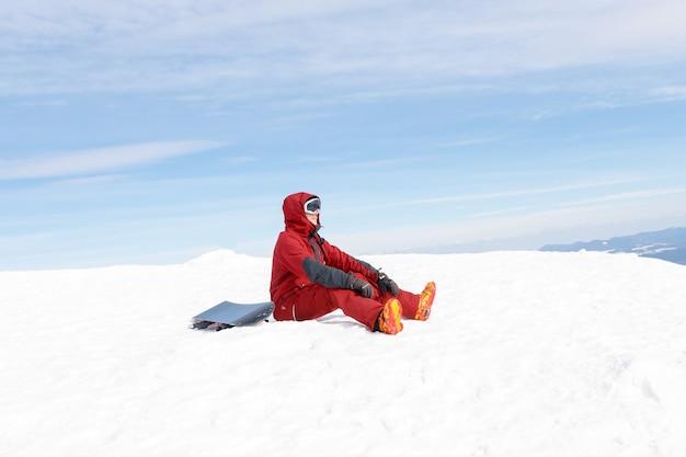 O snowboarder senta-se no alto das montanhas na beira da encosta e olha para longe
