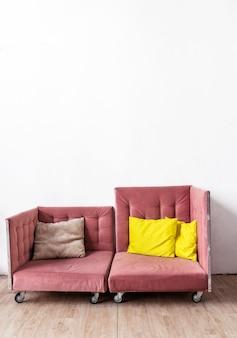 O sofá rosa tem duas partes e fica encostado a uma parede branca. foto vertical