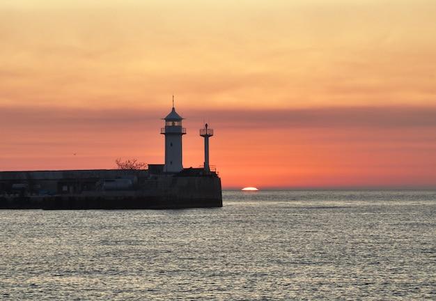 O sol apareceu no horizonte acima da superfície do mar negro no farol de yalta