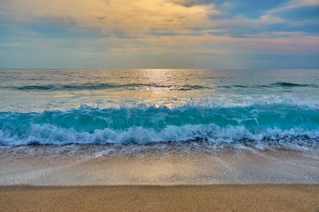 O sol atrás das nuvens reflete na água e nas ondas com espuma batendo na areia.