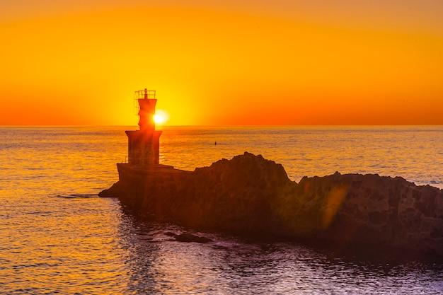 O sol atrás do farol ao pôr do sol na cidade de pasajes san juan. guipúscoa, país basco