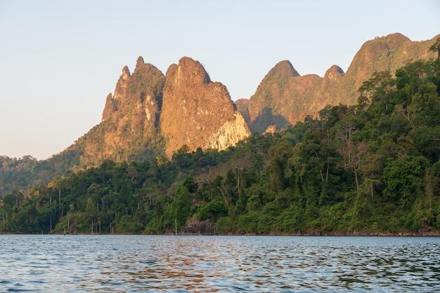 O sol brilha através da floresta e das montanhas no rio.
