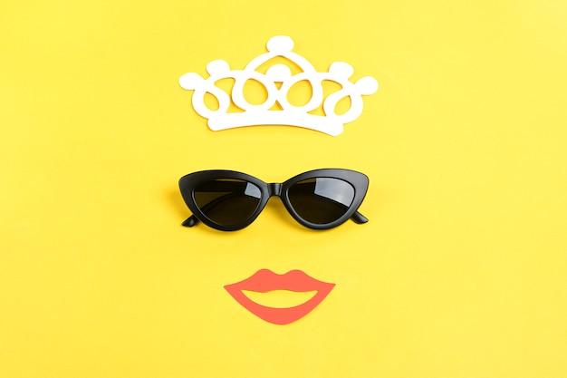 O sol com elegantes óculos de sol pretos, coroa, sorrindo a boca no amarelo flat lay