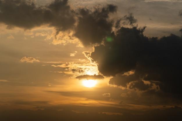 O sol com nuvem na frente do tempo crepuscular.