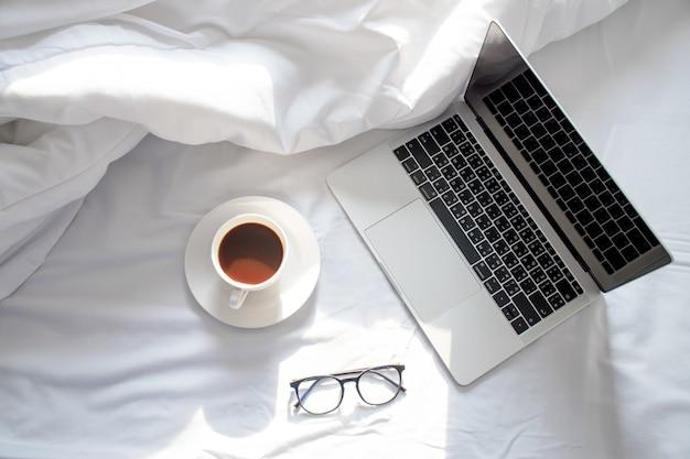 O sol da manhã brilha no laptop e café na cama, o lençol branco na vista superior