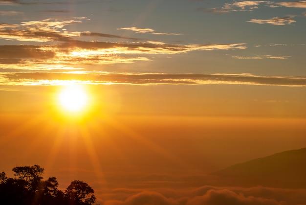 O sol da manhã subindo, havia nuvens e picos de montanhas contra um padrão borrado.