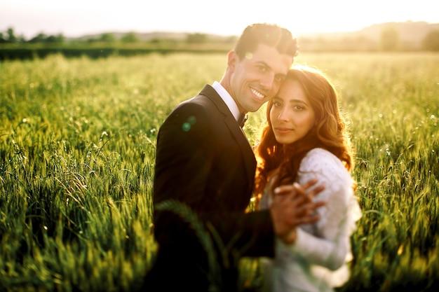 O sol da noite quente ilumina casal casando beijando no campo
