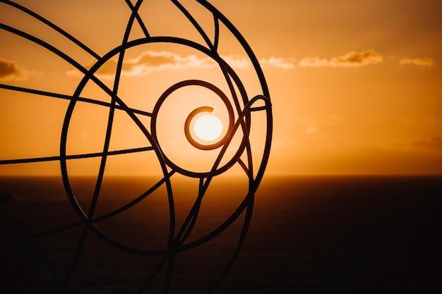O sol durante o pôr do sol coincidindo com uma escultura com espaço de cópia