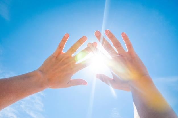 O sol está brilhando entre os dedos