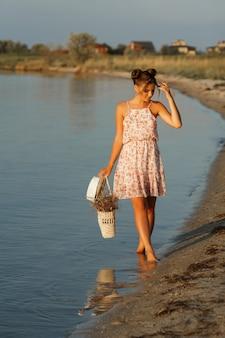 O sol está brilhando no modelo. garota ao pôr do sol à beira-mar com um saco de palha e um chapéu fica com os pés descalços. o fundo está desfocado.