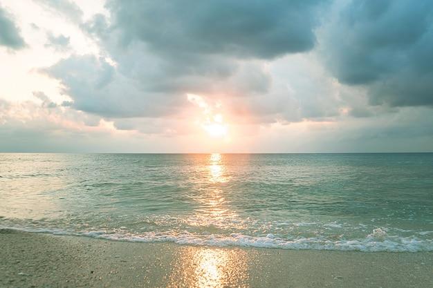 O sol no céu dramático sobre o mar. fundo natural. forças do conceito de natureza. luz clara do entardecer. água limpa e limpa. céu nublado. o mar é calmo.