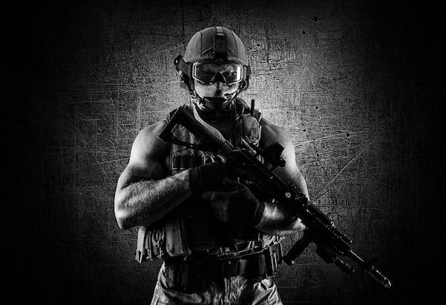O soldado da unidade especial está com uma arma automática em vantagem. mídia mista