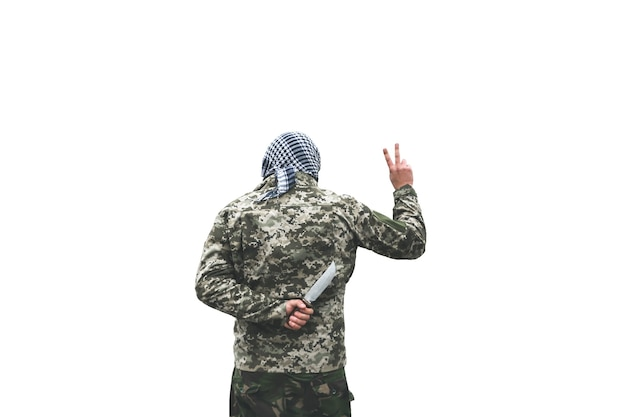 O soldado está de pé com o uniforme de camuflagem, isolado no fundo branco. bandana quadriculada keffiyeh shemagh. homem com faca nas costas no lugar deserto e abandonado. traição de inimigos.