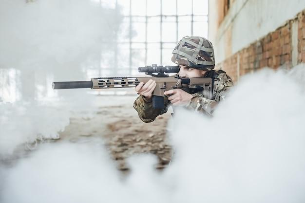 O soldado militar de uniforme mantém um rifle moderno em suas mãos, ele está mirando na fumaça