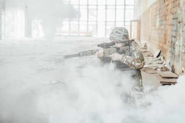 O soldado militar de uniforme mantém um rifle moderno nas mãos, mirando na fumaça.