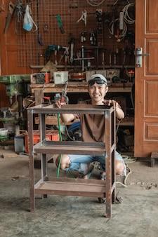 O soldador agachado sorri para a câmera segurando uma grade de ferro para soldar contra o fundo de uma oficina de soldagem