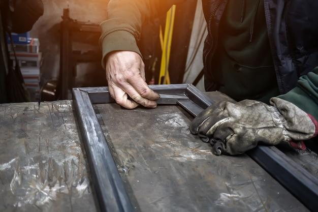 O soldador cozinha o quadro. o soldador cozinha o metal. o soldador cozinha estruturas metálicas. trabalhos de soldagem. faíscas, metal fundido