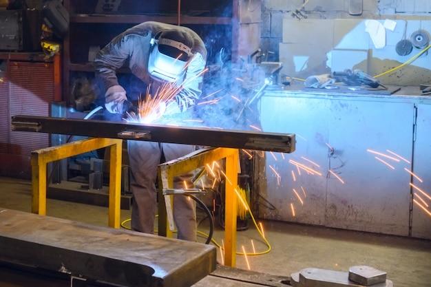 O soldador de trabalho solda as peças na fábrica. um processo de soldagem semiautomática.