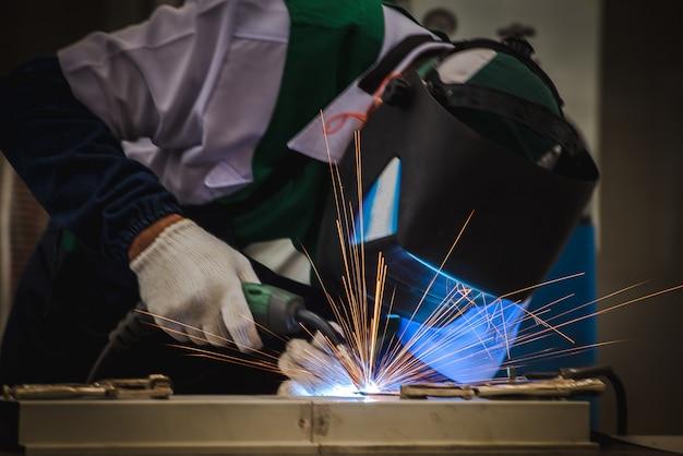 O soldador está soldando as peças metálicas na planta de montagem de automóveis e praticando as habilidades do soldador em plantas industriais.