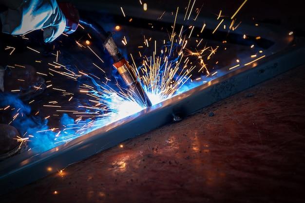 O soldador está soldando placas de aço