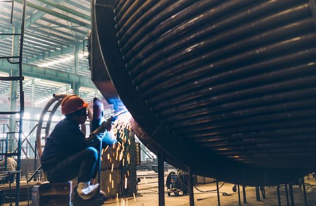 O soldador na obra de máquinas está fazendo o trabalho de soldagem