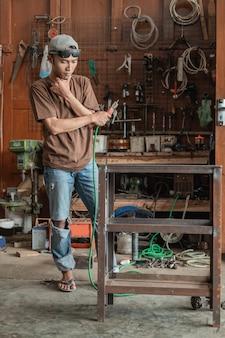 O soldador pensa em como fazer um rack de metal ao segurar um soldador elétrico em uma oficina de soldagem