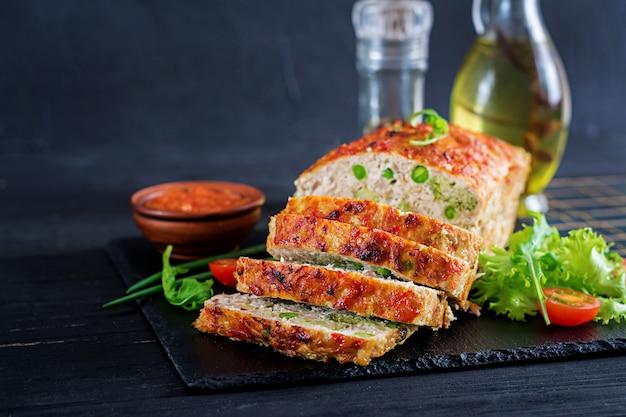 O solo caseiro saboroso cozeu o bolo de galinha com ervilhas verdes e brócolis na tabela preta. pão de carne americana de alimentos.
