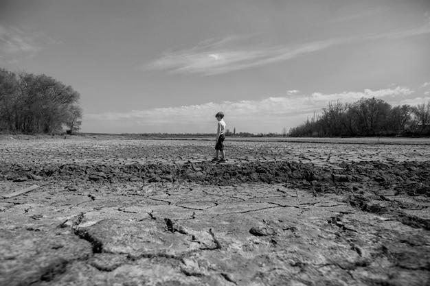 O solo está seco e rachado. o deserto, pano de fundo do aquecimento global. o menino fica no meio.