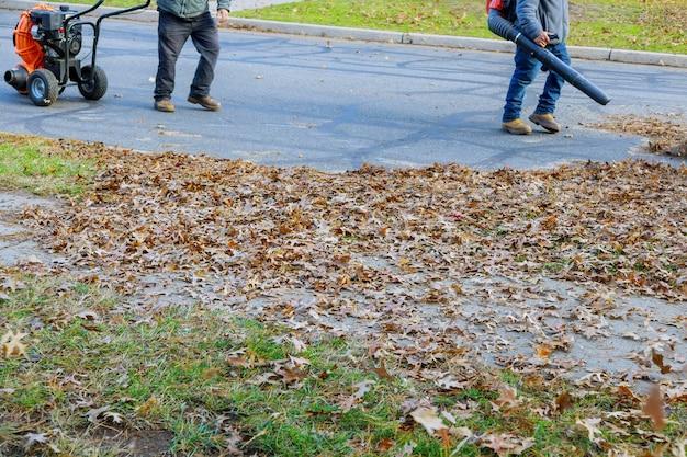 O soprador de folhas sopra o trabalhador caído para limpar uma pilha de folhas caídas