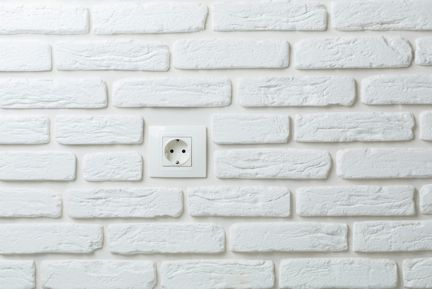 O soquete branco em uma parede de tijolos.