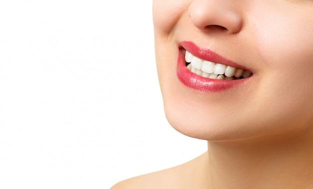 O sorriso de uma jovem mulher com dentes brancos perfeitos.