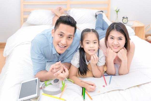 O sorriso feliz da família asiática e relaxa na cama em casa em férias do feriado.