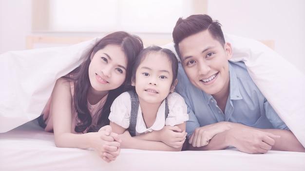 O sorriso feliz da família asiática e relaxa na cama em casa.