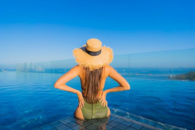 O sorriso feliz das jovens mulheres asiáticas bonitas relaxa em torno da piscina exterior no recurso do hotel para viajar nas férias