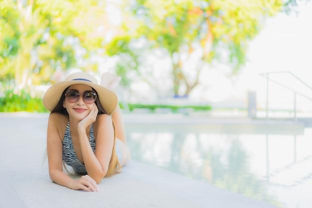 O sorriso feliz das mulheres asiáticas novas bonitas relaxa em torno da piscina exterior no recurso do hotel