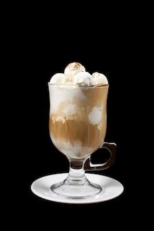 O sorvete de leite no copo na superfície preta