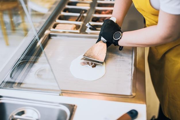 O sorvete frito rola na frigideira. sobremesa de sorvete laminado artesanal na placa fria. máquina de sorvete frito com frigideira de aço resfriada.