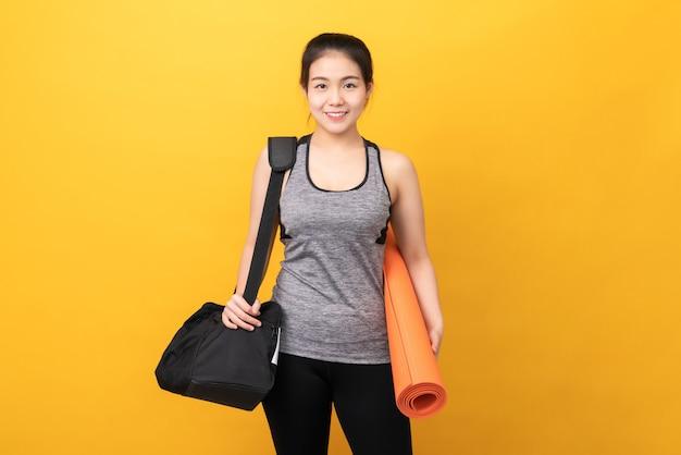 O sportswear vestindo da mulher asiática de smiley que guarda a esteira alaranjada com esportes ensaca no conceito saudável do estilo de vida da parede amarela.