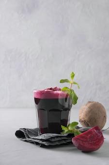 O suco de beterraba decora na hortelã de vidro no cinza. fechar-se. orientação vertical.