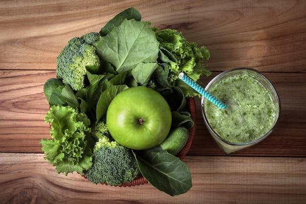 O suco de smoothie verde fresco saudável na garrafa de vidro na mesa de madeira