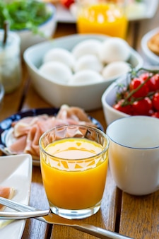 O suco é derramado em um copo de suco de laranja no café da manhã mesa com comida no café da manhã laranja
