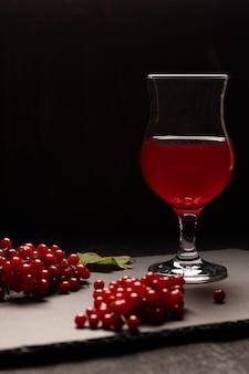 O suco vermelho do viburno com uma taça de vidro em uma mesa preta. perto de bagas de viburnum. comida saudável. vista frontal. copie o espaço