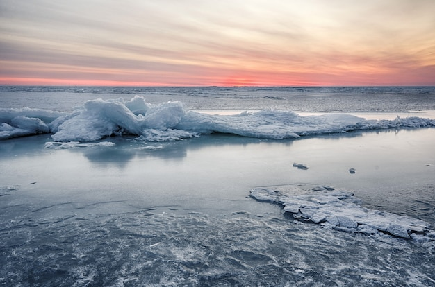 O sumário congelou o seascape do nascer do sol do inverno com gelo e coloriu o céu.