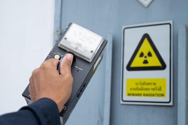 O supervisor usa o medidor de pesquisa para verificar o nível de radiação na zona radioativa