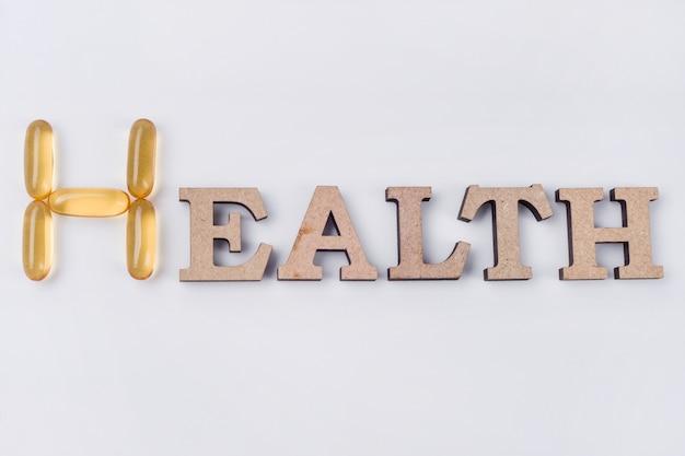O suplemento de vitamina e, palavra saúde, é letras de madeira abstratas e cápsulas de óleo de peixe.