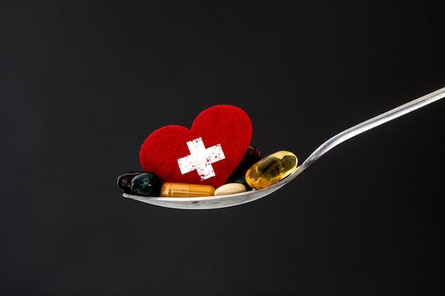 O suplemento médico colorido e comprimidos da droga com coração vermelho na colher
