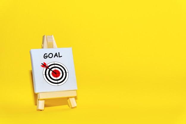 O suporte do sinal com uma flecha no alvo em um fundo amarelo atingiu exatamente o centro. conceito de foco em um alvo