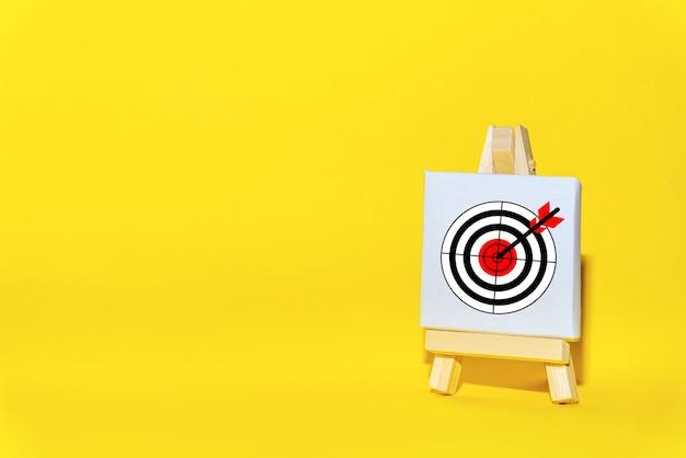 O suporte do sinal com uma flecha no alvo em um fundo amarelo atingiu exatamente o centro. táticas de segmentação de publicidade.