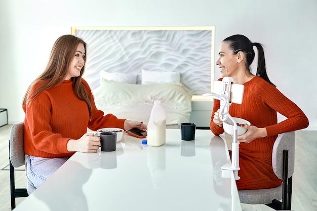 O suporte do telefone é fixado na mesa de jantar onde a família da mãe e da filha tomam cereal matinal com leite